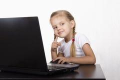 A menina que senta-se na tabela, trabalhando em um portátil, e olhado direito Fotografia de Stock Royalty Free