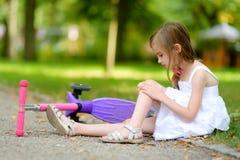 Menina que senta-se na terra depois que caiu ao montar seu 'trotinette' fotografia de stock