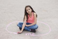 Menina que senta-se na terra e no espaço pessoal de tiragem imagem de stock royalty free