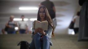 Menina que senta-se nas escadas no metro e que lê um livro filme