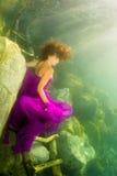 Menina que senta-se nas escadas sob a água Fotos de Stock