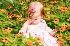 Menina que senta-se nas flores imagem de stock