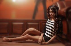 Menina que senta-se no assoalho contra a parede com paneling e o papel de parede de madeira Imagem de Stock Royalty Free