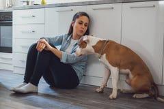 Menina que senta-se no assoalho da cozinha que beija seu cão imagens de stock