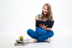 Menina que senta-se no assoalho e que escreve notas Fotografia de Stock