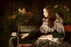 Menina que senta-se no banch em um parque da noite e que toma um copo de chá Foto de Stock Royalty Free