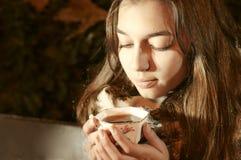 Menina que senta-se no banch em um parque da noite e que toma um copo de chá Imagem de Stock Royalty Free