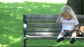 Menina que senta-se no banco de parque vídeos de arquivo