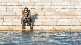 Menina que senta-se no banco de rio Fotografia de Stock Royalty Free