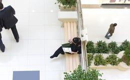Menina que senta-se no banco e que lê um compartimento fotografia de stock