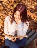 Menina que senta-se no banco na arca e que lê um livro Imagens de Stock Royalty Free