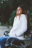 Menina que senta-se no banco no parque da cidade no tempo frio Fotos de Stock