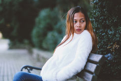Menina que senta-se no banco no parque da cidade no tempo frio Imagens de Stock Royalty Free