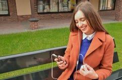 Menina que senta-se no banco, sorriso, guardando um telefone Fotografia de Stock