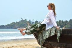 Menina que senta-se no barco de pesca velho Imagem de Stock
