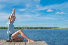 Menina que senta-se no cais, em uma pose da ioga, no fundo da natureza fotografia de stock