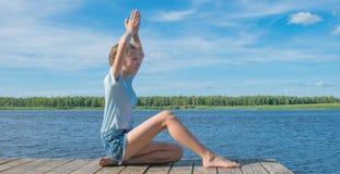 Menina que senta-se no cais, fazendo a ioga, contra a água e o céu, há um lugar para a inscrição fotografia de stock royalty free