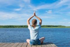 Menina que senta-se no cais, levantando suas mãos acima, contratado na meditação, contra o lago fotos de stock