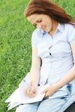 A menina que senta-se no campo Fotos de Stock