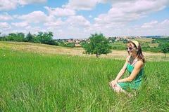 Menina que senta-se no campo do país Imagem de Stock