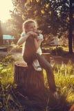 Menina que senta-se no coto na floresta Foto de Stock