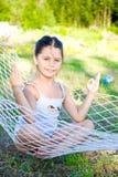 Menina que senta-se no hammock Fotografia de Stock