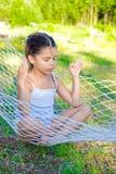 Menina que senta-se no hammock Fotos de Stock Royalty Free