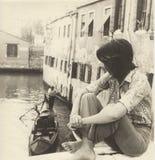 Menina que senta-se no lado de uma ponte em Veneza que olha uma passagem da gôndola, nos anos 60 imagem de stock royalty free