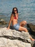 Menina que senta-se no mar Fotos de Stock Royalty Free