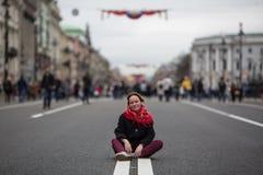Menina que senta-se no meio da rua Passeio imagens de stock