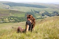 Menina que senta-se no monte Imagem de Stock Royalty Free