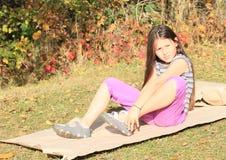 Menina que senta-se no papel Imagens de Stock