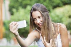A menina que senta-se no parque e faz o selfie Fotografia de Stock Royalty Free