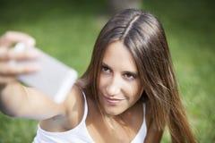 A menina que senta-se no parque e faz o selfie Imagens de Stock