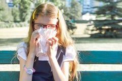 Menina que senta-se no parque que espirra com lenço, alergias sazonais fotografia de stock royalty free