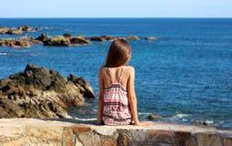 Menina que senta-se no penhasco na parte dianteira de oceano no mar do penhasco do recurso de Los Cabos México imagem de stock