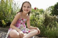 Menina que senta-se no prado foto de stock royalty free