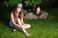 Menina que senta-se no prado gramíneo ao lado de uma árvore e de um G Imagem de Stock