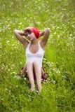 Menina que senta-se no prado gramíneo Fotografia de Stock Royalty Free