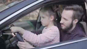 Menina que senta-se no regaço do pai no fim do carro acima A crian?a est? aprendendo conduzir o carro Despesa de sorriso do homem video estoque