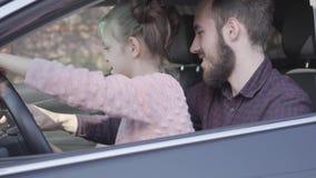 Menina que senta-se no rega?o do pai no fim da roda da terra arrendada do carro acima A crian?a est? aprendendo conduzir o carro  video estoque