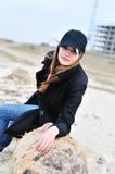 Menina que senta-se no registro Foto de Stock
