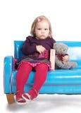 Menina que senta-se no sofá Fotos de Stock Royalty Free