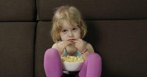 Menina que senta-se no sofá e que come sopros do milho Puffcorns do sorriso e do gosto da criança filme
