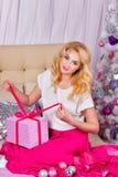A menina que senta-se no sofá e desembala presentes do Natal Fotos de Stock Royalty Free