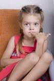 A menina que senta-se no sofá e olha pensativamente à esquerda Fotografia de Stock