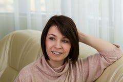 Menina que senta-se no sofá em casa fotografia de stock royalty free