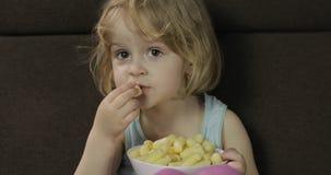 Menina que senta-se no sof? e que come sopros do milho Crian?a que olha a tev?, puffcorns do gosto video estoque