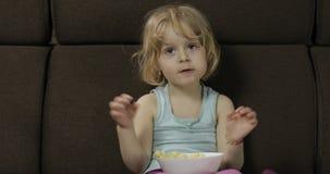 Menina que senta-se no sof? e que come sopros do milho Crian?a que olha a tev?, puffcorns do gosto filme