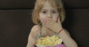 Menina que senta-se no sof? e que come sopros do milho Puffcorns do sorriso e do gosto da crian?a filme
